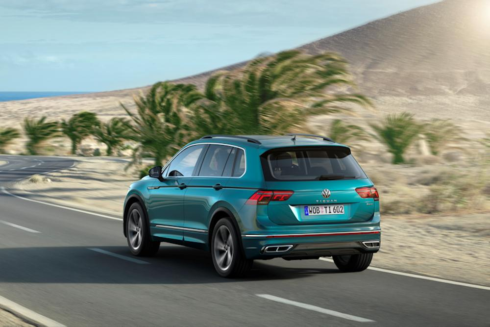 Blue Volkswagen Tiguan driving along desert road with palm trees