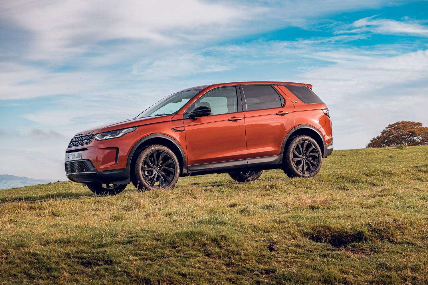 orange land rover discovery sport on grass with blue sky
