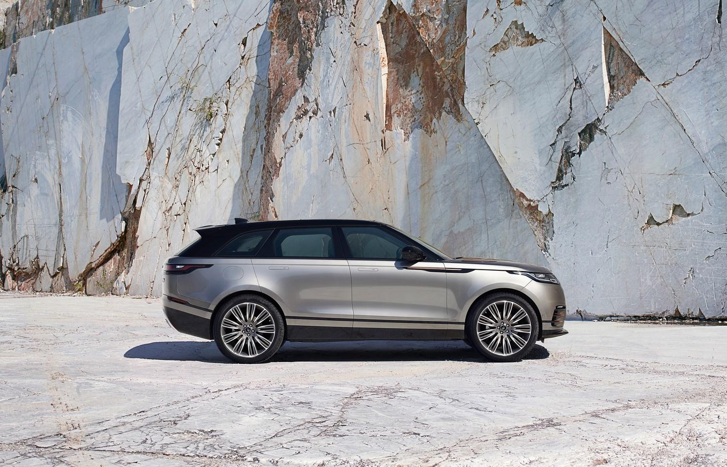 Silver Range rover velar parked in front of a granite cliff