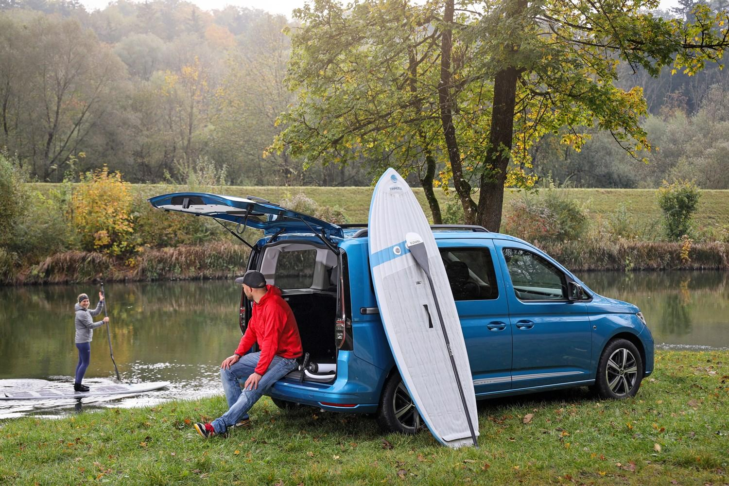 Blue Caddy Cargo parked by a river with a man sat in the boat with a paddle board