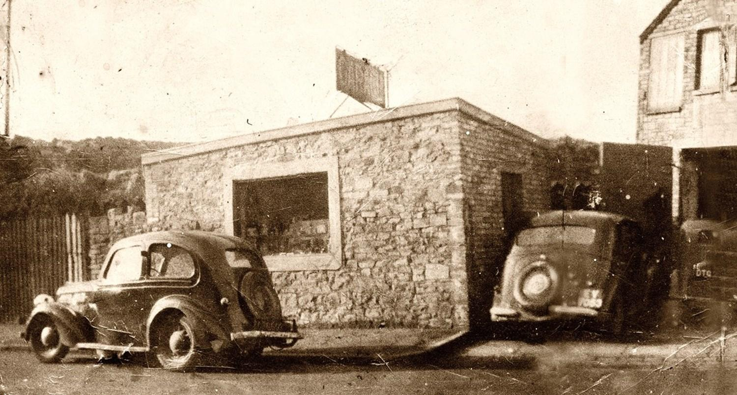 Black and white photo of cars outside an old building