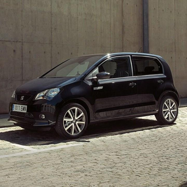 Black SEAT Mii Electric parked by wall