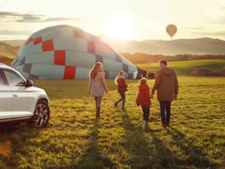 Family walking towards hot air balloon