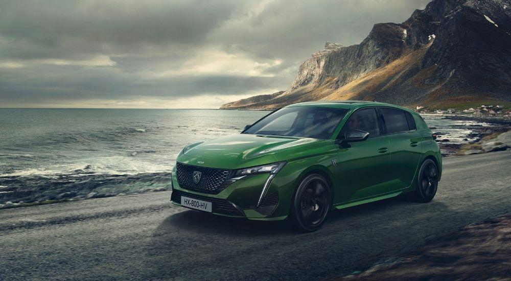 Green new 308 driving along the coastline