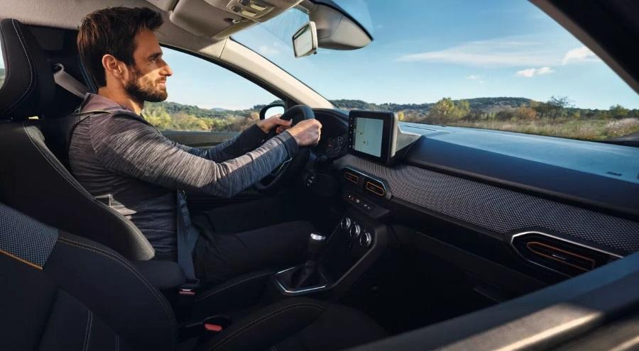 Man sat driving a Dacia Sandero Stepway
