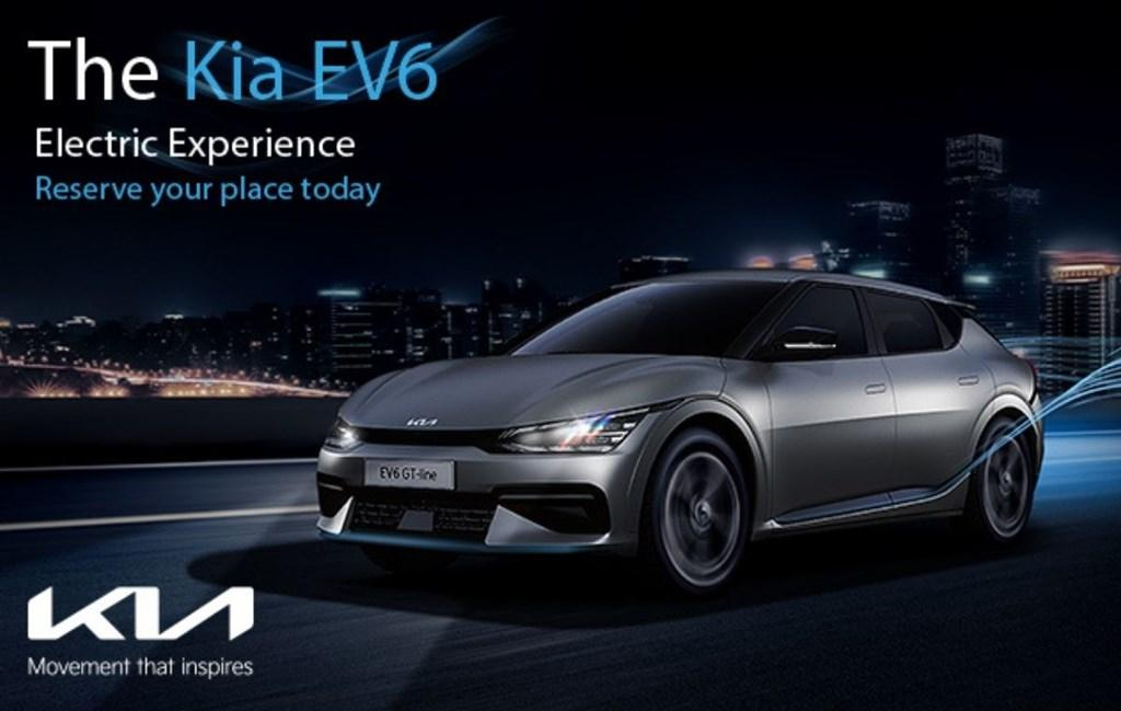 Silver Kia EV6 electric vehicle shown on a black background. The white Kia logo sits in the bottom left corner. In the top right, text reads: