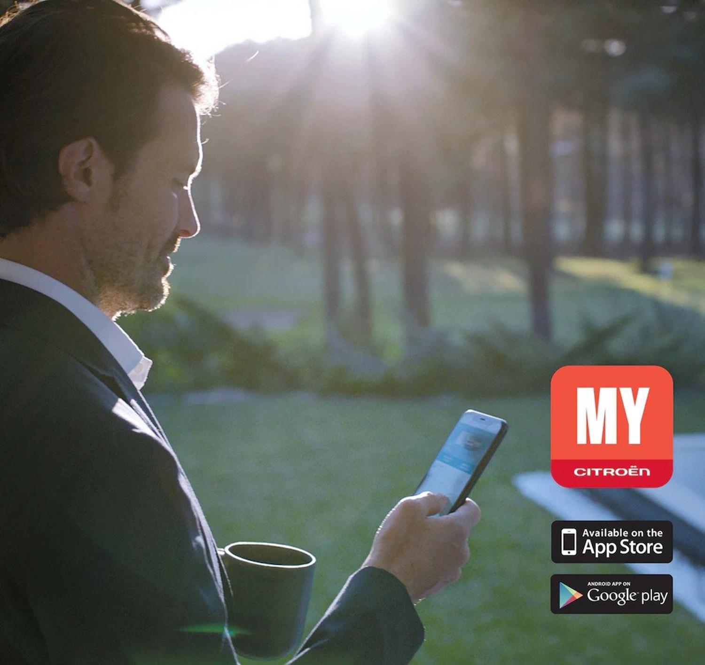 A man using the Citroen Mycar app on his smartphone