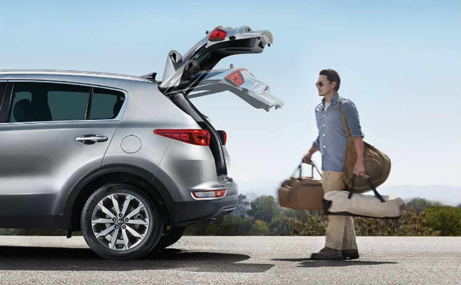 A man using the Kia liftgate feature to open the boot of his car