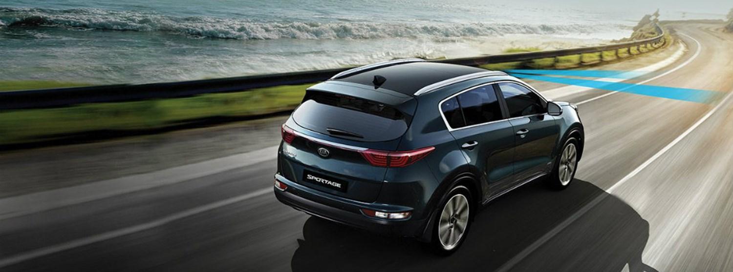 A Kia Sportage driving outdoors highlighting the Lane Keep Assist feature