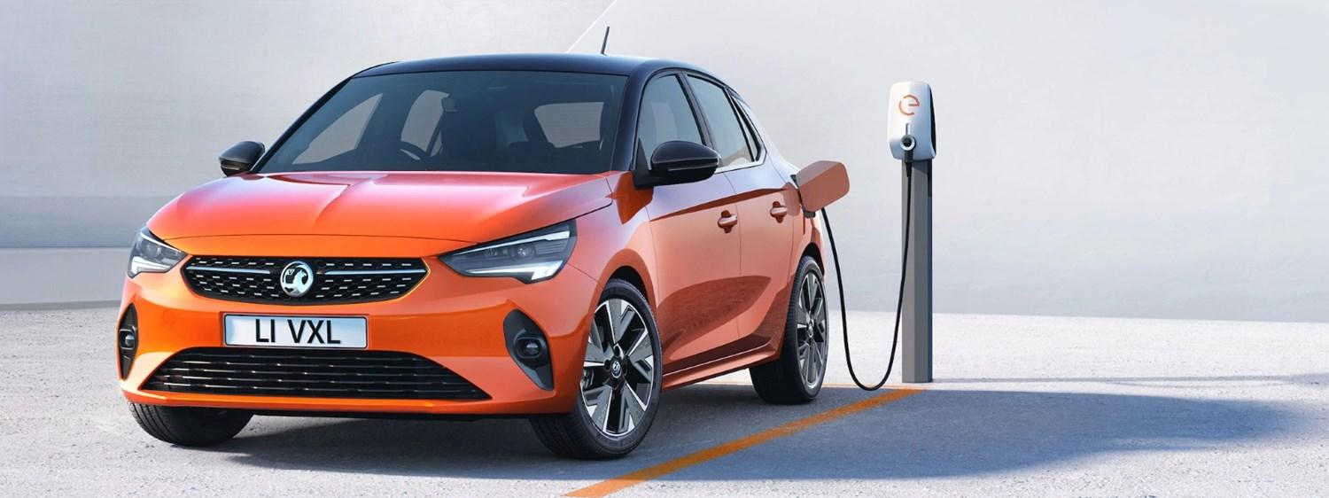an orange Corsa-e parked & plugged-in to a charge point