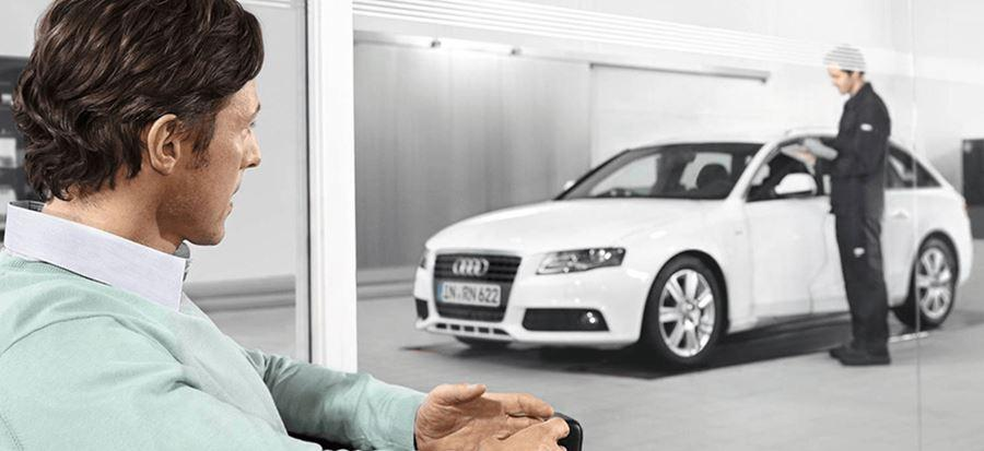 Man in mint jumper sat looking at white audi with technician