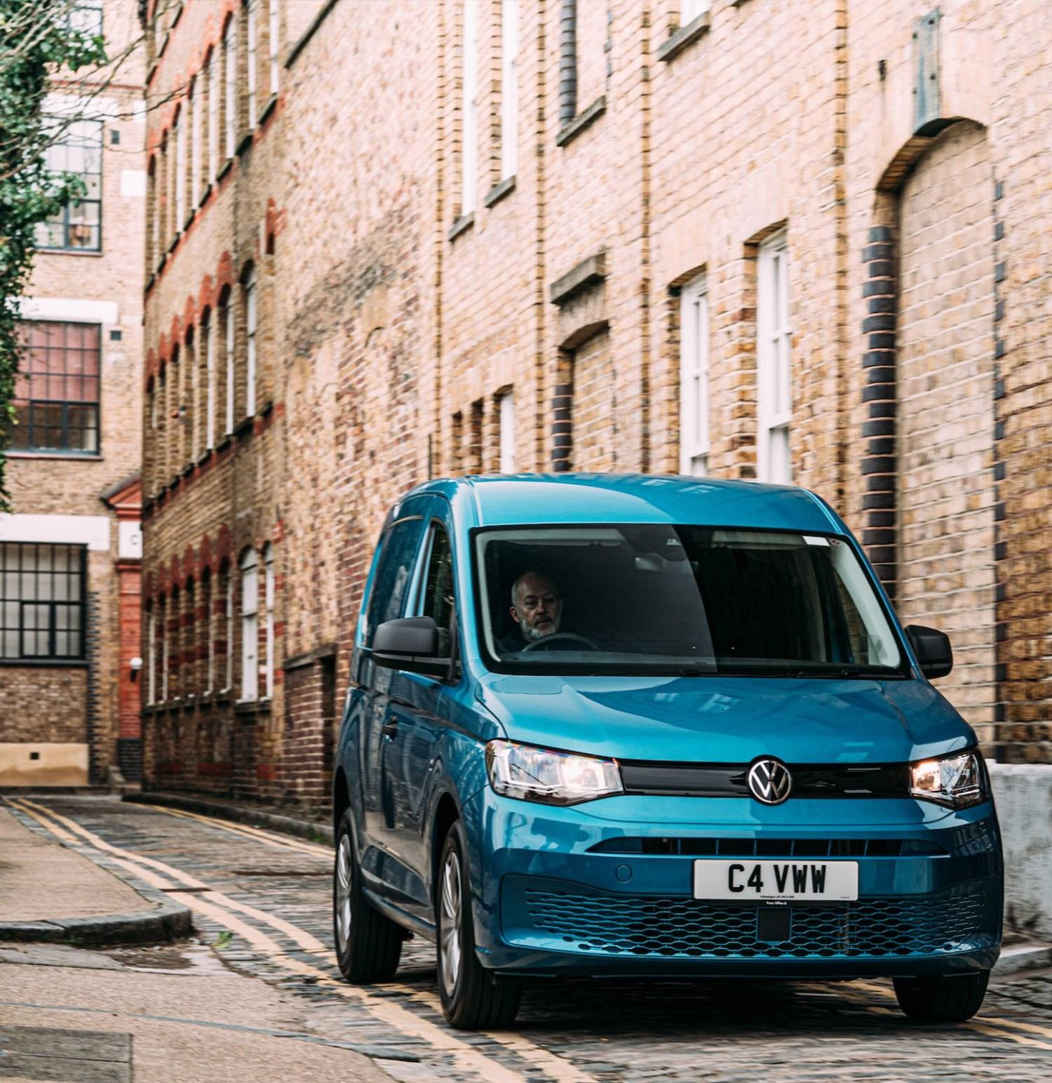 Blue Volkswagen Caddy front view on cobbled road