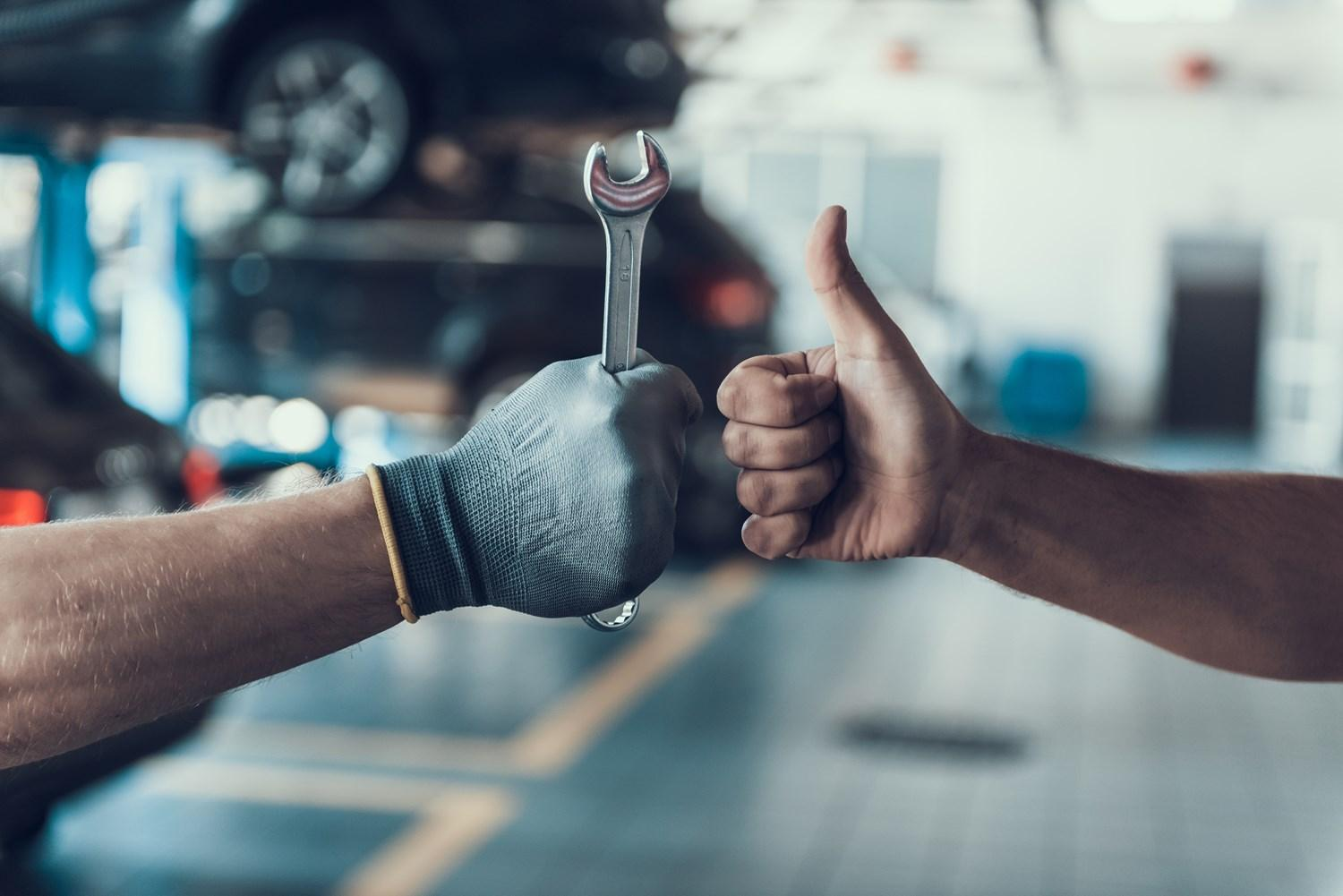 Man holding a wrench and a thumbs up