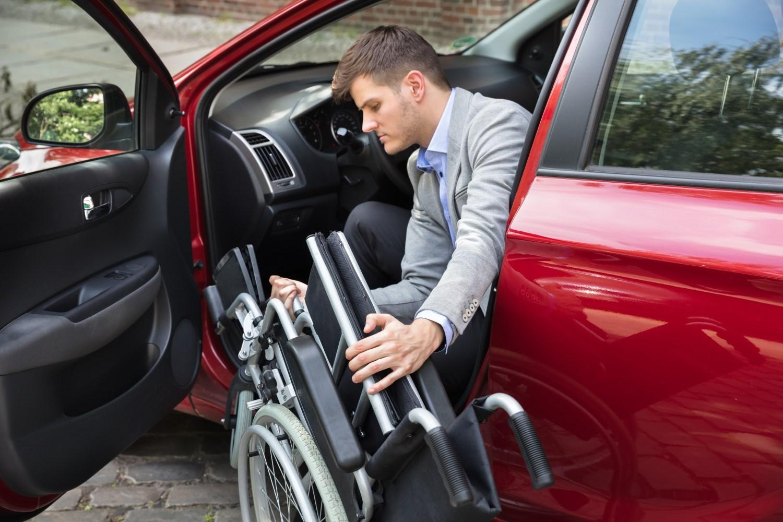 Man folding wheelchair into red car